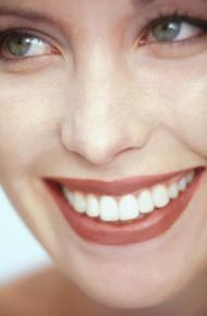 Closeup of a woman smiling to show the connection between oral and overall health.