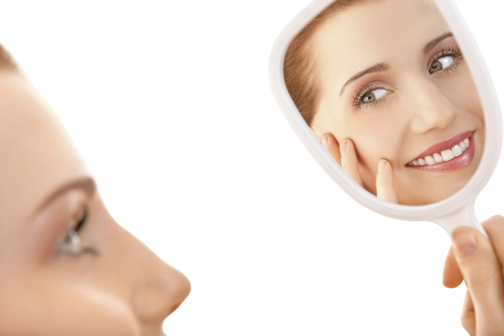 A woman looking in the mirror shows how cosmetic dentistry from our Redmond WA dentist can enhance your smile.