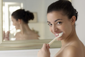 A woman brushing her teeth in the mirror shows the importance of proper dental hygiene.