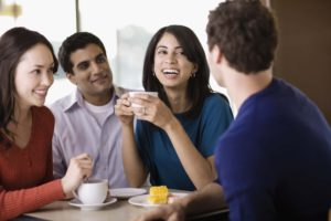 A group of friends at a coffee house laughing to show how Invisalign can help you make a great first impression