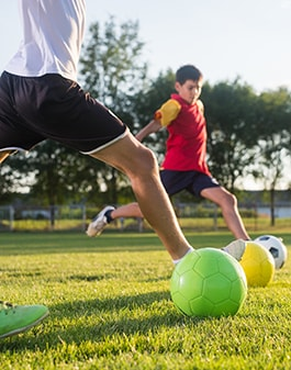 Children playing soccer while customized mouthguards are protecting their smiles