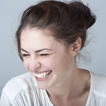 General dentistry ensures you and your family have healthy smiles just like this photo of a laughing woman.